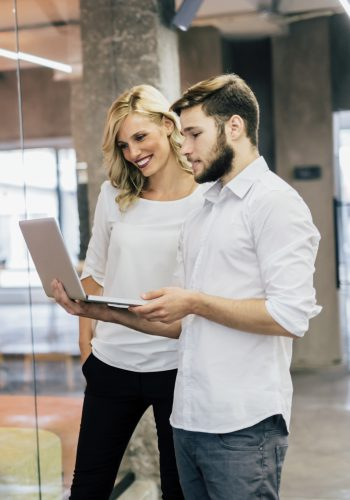 Cowerkers looking at notebook in a modern office